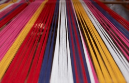 The coloured cotton is positioned on the loom before the pattern making process begins.